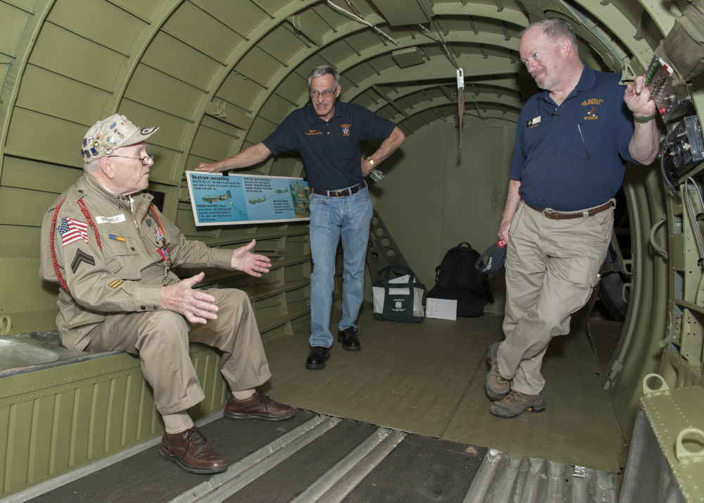 George Shenkle, left, talks to Bill Lee, Air Mobility Command Museum volunteer, center, and Bob Leicht, AMC Museum volunteer, inside a C-47A Skytrain April 18, 2015, at the AMC Museum on Dover Air Force Base, Del. Lee and Leicht are part of a restoration team that recently restored the interior of the aircraft to an accurate World War II-era presentation. (U.S. Air Force photo/Airman 1st Class Zachary Cacicia)