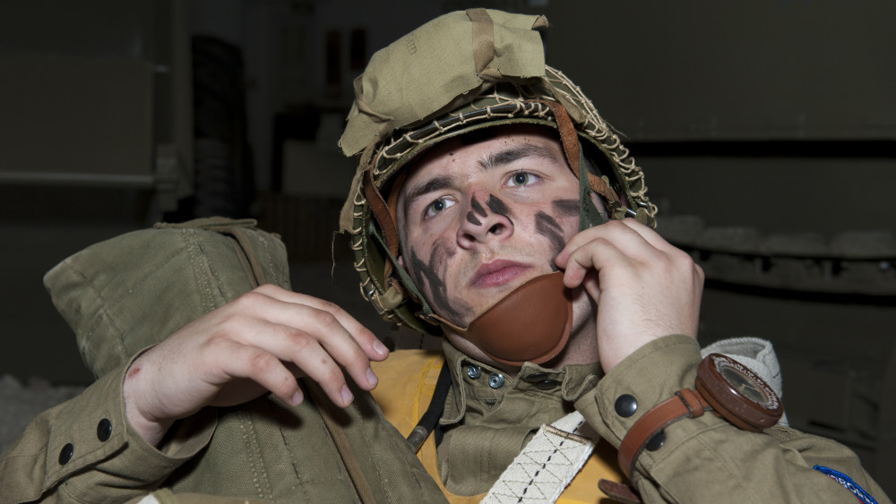 Christian Holland adjusts the chin strap of his combat helmet April 18, 2015, at the Air Mobility Command Museum on Dover Air Force Base, Del. Holland, 16, travelled from Hummelstown, Pa. to take part in the event. (U.S. Air Force photo/Airman 1st Class Zachary Cacicia)