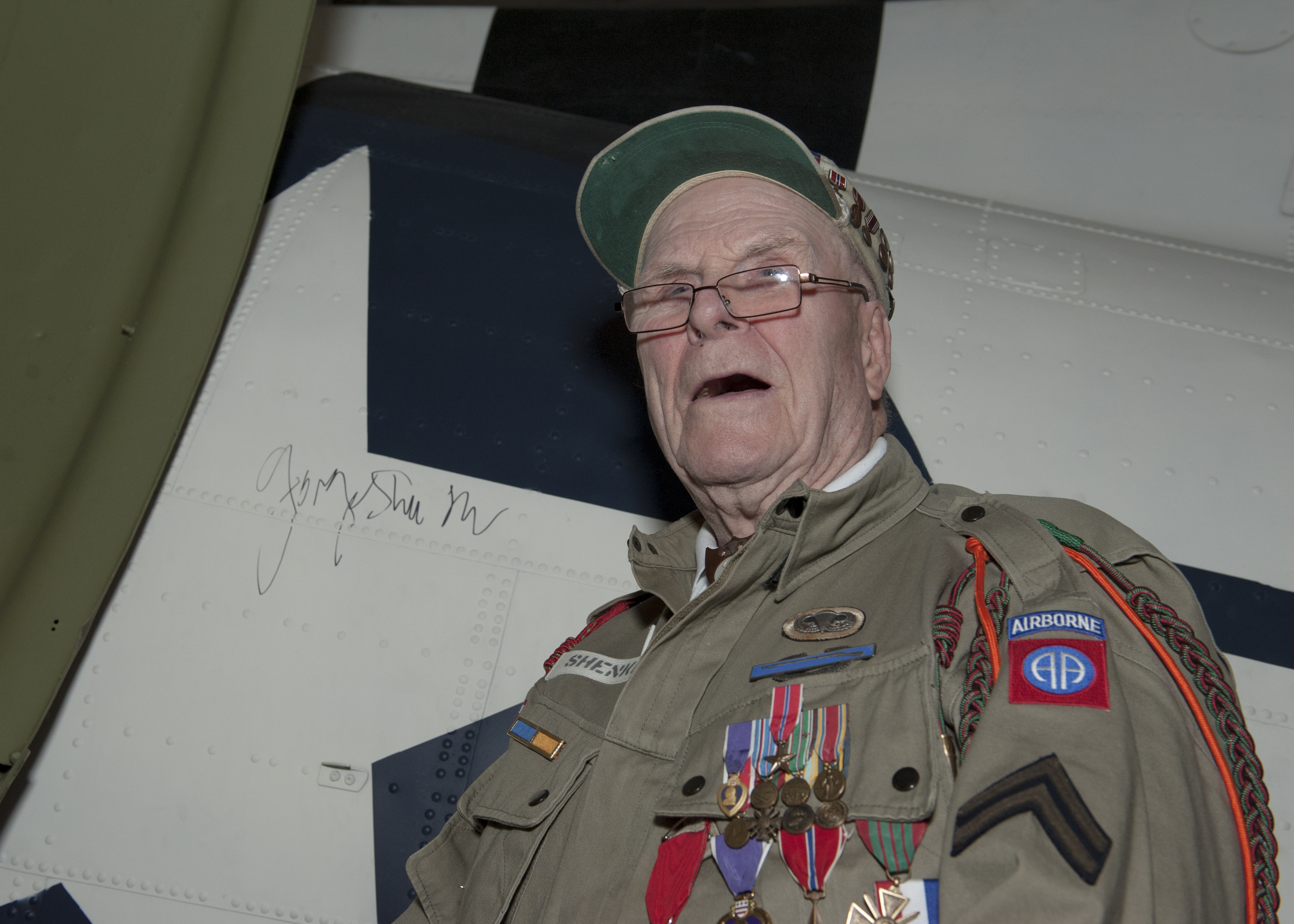 George Shenkle poses after autographing the roundel on the side of a C-47A Skytrain April 18, 2015, at the Air Mobility Command Museum,  near Dover Air Force Base, Del. Shenkle signed the roundel in the same fashion that he and his fellow paratroopers signed  hours before jumping into Normandy, France on D-Day, June 6, 1944. (U.S. Air Force photo/Airman 1st Class Zachary Cacicia)